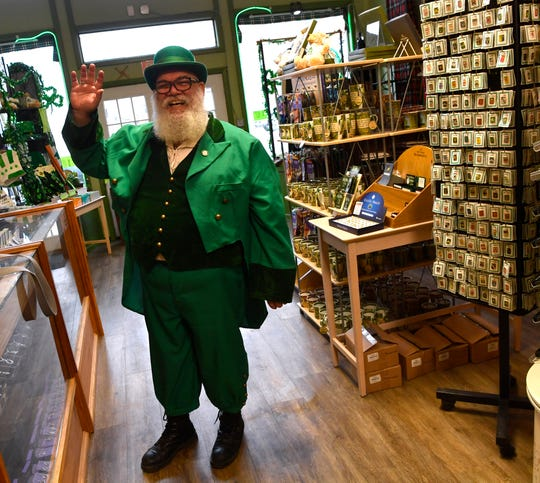 Orion Gallagher gives an enthusiastic wave from inside Things Celtic, an Irish-themed store in Dublin Saturday.