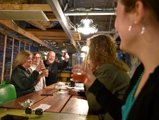 Brad Asselin of Marshall raises a glass for cheers at Dark Horse Brewing Co. as part of the 'Luck of the Irish Marshall Trolley Beer Tour in Marshall, Mich. on Saturday, March 14, 2020.