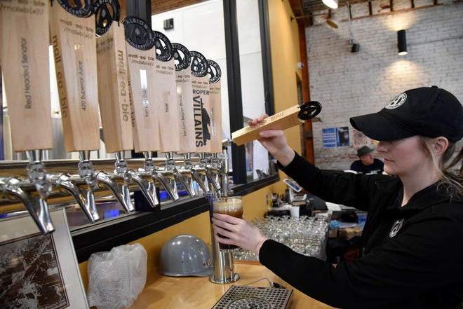 Albion Malleable Brewing Co. bartender and server Erin Markovich pours 'Pitter Patty' dry stout from the tap in Albion, Mich. on Saturday, March 14, 2020.