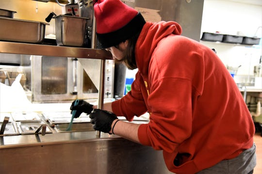 Eric Barringer of Territorial Brewing Co. serves dipping sauce to a customer in Springfield, Mich. on Saturday, March 14, 2020.