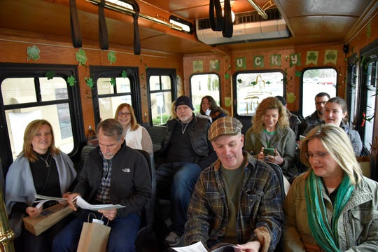 Passengers on the 'Luck of the Irish Marshall Trolley Beer Tour' look through information packets containing food and tap menus en rout to Albion Malleable Brewing Company in Albion on Saturday, March 14, 2020.