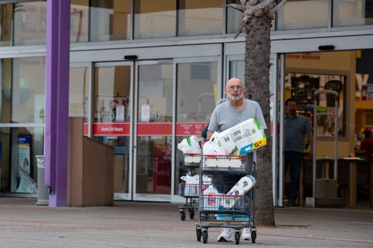 People leave HEB on Saratoga Boulevard with paper goods and water on Sunday, March 15, 2020.