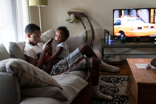 Demario Hill, 17, watches his brother Raynard Hill, 14 months, as their mother Donyetta Hill (not in the photo) prepares snacks for them at home in Detroit, Friday, March 13, 2020.