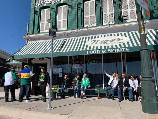 St. Patrick's Day revelers gather outside of Nemo's restaurant on Sunday, even though the annual St. Patrick's Day Parade was cancelled this year due to the coronavirus outbreak. The state is tightening up rules on public gatherings because of the pandemic.