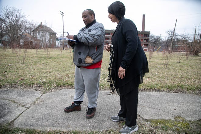 Frederick Campbell, 45, signs a petition handed to him from Venita Thompkins, 55, Thursday, March, 12, 2020. Thompkins encouraged Campell to attend a zoning meeting to be held at Detroit City Hall later in March to oppose the developer of Detroit's Herman Kiefer Complex who is proposing a tree nursery on vacant land surrounding the development. Some residents are opposed to the plan they say the nursery won't benefit the neighbors that it is only in the economic interest of the developer.