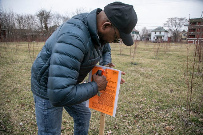 George Adams, 47, of Detroit attaches a sign to a wooden post on Thursday to alert neighbors of a zoning meeting to be held at Detroit City Hall later in March to oppose the developer of Detroit's Herman Kiefer Complex who is proposing a tree nursery on vacant land surrounding the development. Some residents are opposed to the plan they say the nursery won't benefit the neighbors.