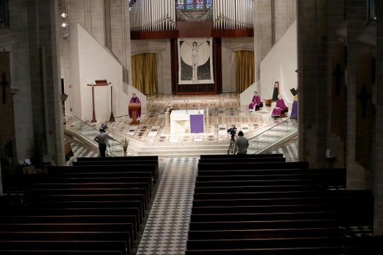 Catholic Archbishop of Detroit Allen Vigneron's service on Sunday was livestreamed from Detroit's Cathedral of the Most Blessed Sacrament Church, where pews were empty because of the coronavirus pandemic.