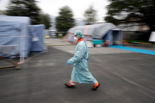 A hospital worker wearing a mask and protective clothing walks between the emergency structures that were set up to ease procedures at the Brescia hospital in northern Italy on Thursday.