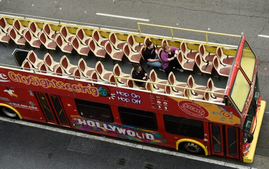 Passengers sit in a mostly empty sightseeing bus on Hollywood Boulevard, Thursday, March 12, 2020, in the Hollywood section of Los Angeles.