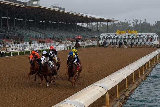 Horses run in the fourth race at Santa Anita Park in front of empty stands Saturday in Arcadia, Calif. While most of the sports world is idled by the coronavirus pandemic, horse racing runs on.