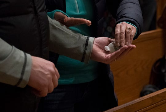 Debbie Hair, right, squeezes hand sanitizer in the palm of her husband Allen, left, during Mass at Members attend Mass at St. Benedict Cathedral in Evansville, Ind., Saturday evening, March 14, 2020. Despite other worship centers closing their doors, St. Benedict's has decided to stay open for now and operate under Gov. Eric Holcomb's executive order to limit gatherings to under 250 people due to the threat of the coronavirus.