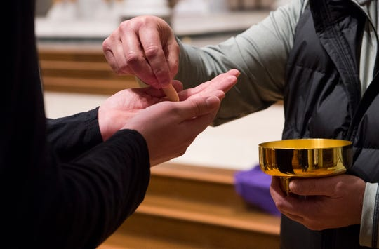 The Eucharist is placed in the palms and not the mouth as a precaution due to the threat of the coronavirus at St. Benedict Cathedral in Evansville, Ind., Saturday evening, March 14, 2020.