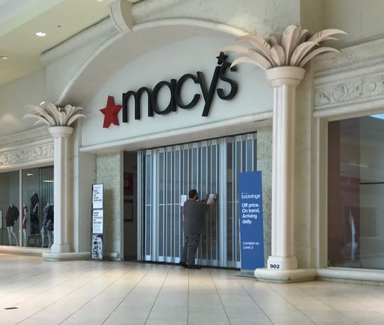 A Macy's worker posts a sign on the department store's Edison Mall inside entrance saying it would open Sunday.  A short time later a MAcy's store manager removed the sign and posted another saying the store would reopen Monday. The Florida Department of Health in Lee County announced Sunday morning that a report of a possible COVID-19 exposure to a Macy's Edison Mall employee was not true.