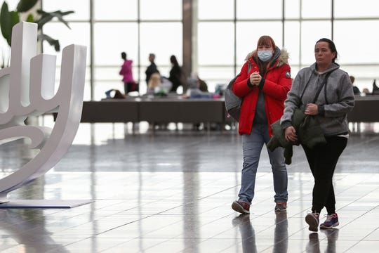 Travelers pass through Indianapolis International Airport on Saturday, March 14, 2020. Low flight rates and increased cancellations are two effects of the coronavirus outbreak on the travel industry.