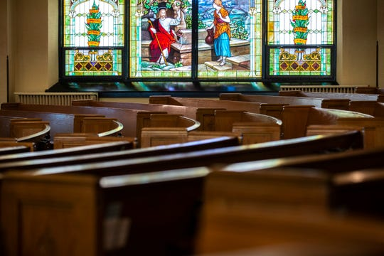 A stained glass window is seen past empty pews during a service, Sunday, March 15, 2020, at the First United Methodist Church in Iowa City, Iowa. The service was live streamed online without community members in the sanctuary after a case of community spread of coronavirus, COVID-19, had been reported in Iowa.