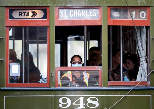 A streetcar conductor wears a mask on St. Charles Avenue in New Orleans on Saturday, March 14, 2020, amid an outbreak of the COVID-19 coronavirus.