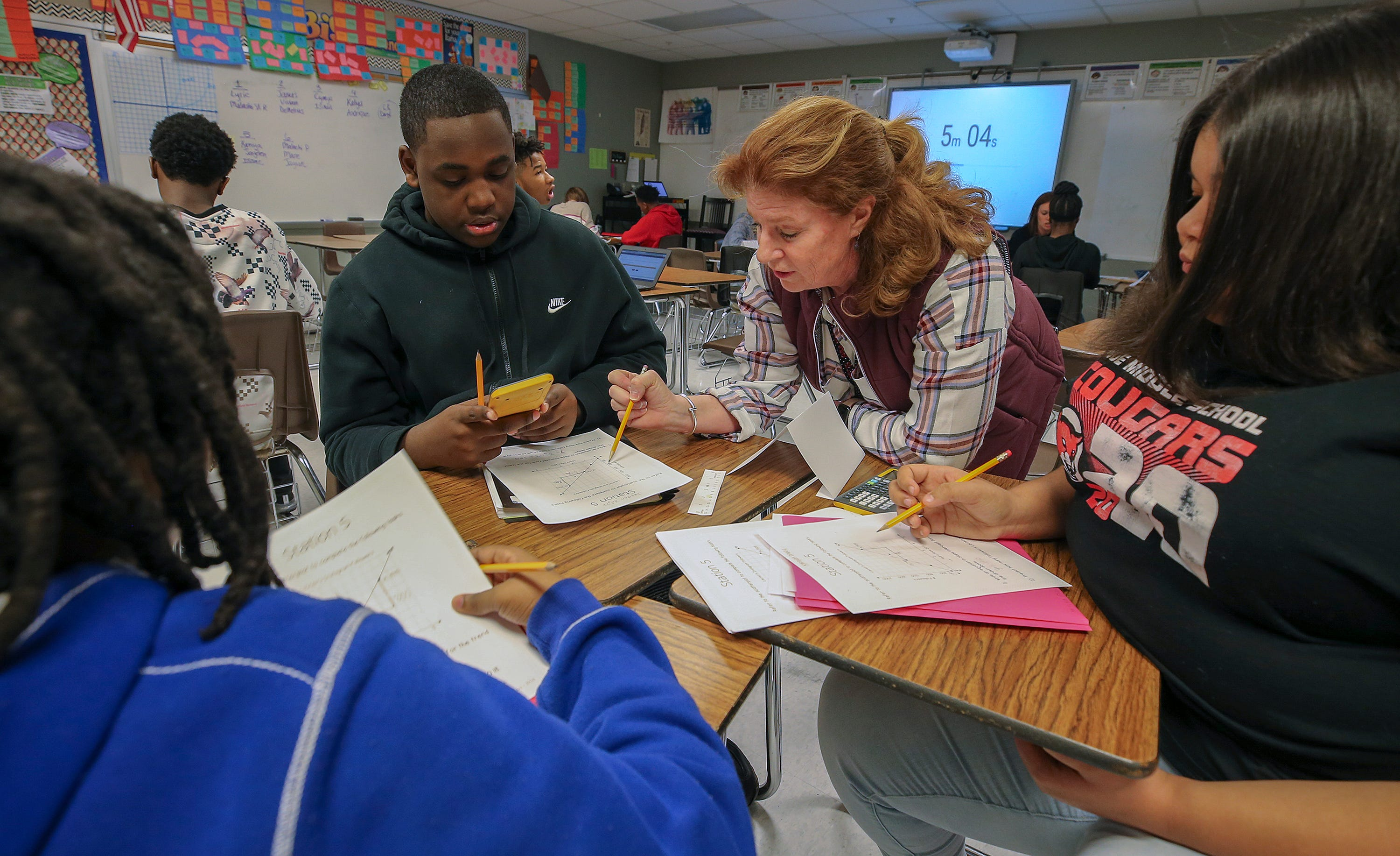 Teacher Shellie Lipka works with Issac Lacy, Jayden Wright  and Kamiya Dailey in a class at Noe Middle School on March 6, 2020.