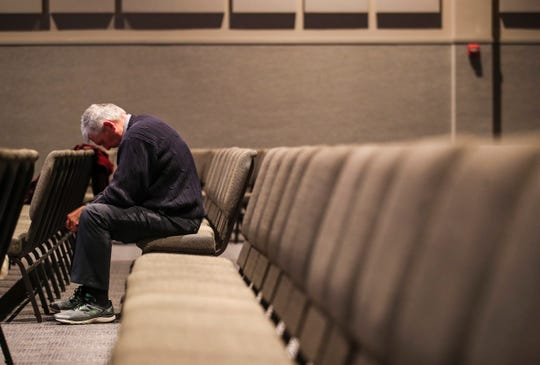 A congregation member bows in prayer at Wesley Chapel during Sunday's service. March 15, 2020.