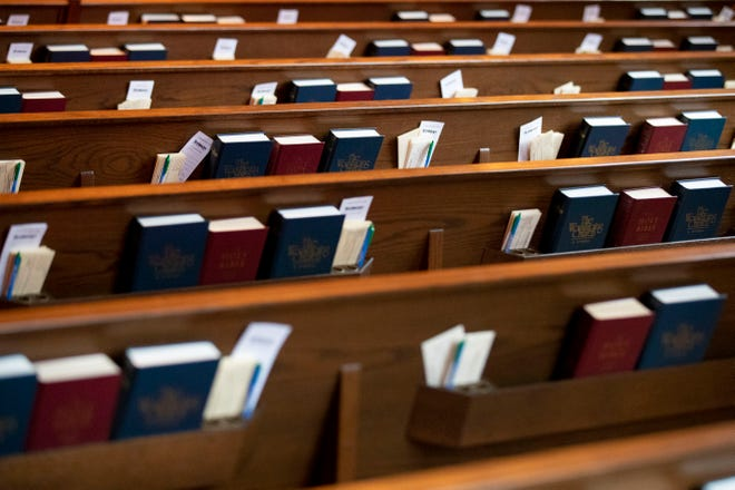 Bibles and prayer books sit in the back of empty pews.