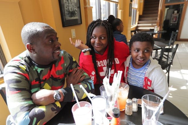 Oliver Edwards, left, of Milwaukee sits with his children, Olivia, 14, and Brady James, 11, at Coffee Makes You Black on North Teutonia Avenue in Milwaukee on Sunday. The spread of coronavirus has led organizers around the world to cancel events. Gov. Tony Evers on Friday ordered the state Department of Health Services to close all K-12 schools, public and private, to help contain the spread of the coronavirus.