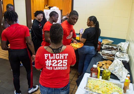 Lee basketball players dig in to some food during a celebration for Lee's state championship year at Sheridan Heights Community Center in Montgomery, Ala., on Sunday, March 15, 2020.