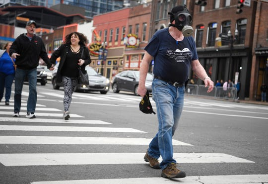 "Singer-songwriter Bert Kencke wears a gas mask on Lower Broadway after Nashville Mayor John Cooper on Sunday asked bars to close and restaurants to limit capacity. """"Don't let the scare of the virus keep you from having a good time,"" Kencke said, adding he was wearing the mask to protect his voice."