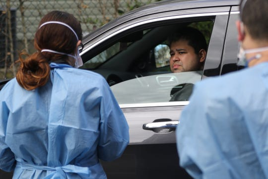 A man (who gave permission to be photographed, but wished not to give his name) is shown as he listens to medical staff, at a coronavirus  testing drive-through, at Riverside Medical Group, in Secaucus. Sunday, March 15, 2020