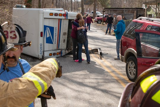 Postal services employees embrace next to a flipped USPS mail service truck after it was involved in a crash with an SUV on the 1000 block of Green Springs Road, Sunday, March 15, 2020, in Berwick Township. One person was taken to the hospital in an ambulance, according to United Hook & Ladder Chief Steve Rabine.
