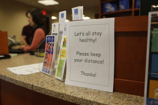 A sign at the front desk on the ground floor of Adriance Memorial Library in the City of Poughkeepsie reminds patrons to keep their distance as seen on Sunday, March 15, 2020.