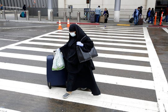 A traveler crosses the street outside Los Angeles International Airport on Saturday, March 14, 2020, in Los Angeles. (AP Photo/Marcio Jose Sanchez)
