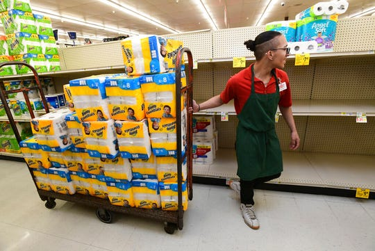 Abraham Ortiz, an employee at Market Basket in Johnstown, Pa., stocks paper towels and toilet paper, Saturday, March 14, 2020. Those items, along with tissues, anti-bacterial soap and hand sanitizer, are selling exponentially faster than normal due to the nation-wide panic over the coronavirus. (John Rucosky/The Tribune-Democrat via AP)