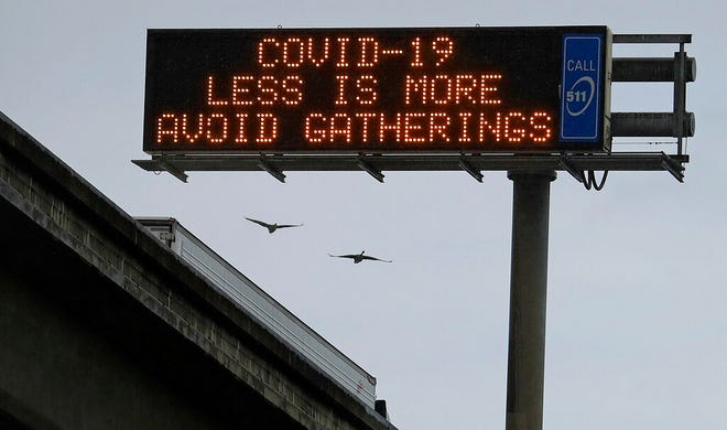 A sign suggesting motorists avoid gatherings is seen on westbound Interstate-880 on Saturday, March 14, 2020, in Oakland, Calif. (AP Photo/Ben Margot)