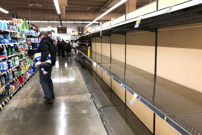 A shopper looks over cleaning supplies as shelves that once supported an abundance of toilet paper and paper towels lay empty at a Chicago area grocery store Saturday, March 14, 2020. (AP Photo/Charles Rex Arbogast)