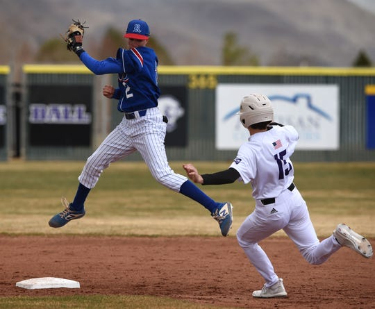 Reno senior Patrick Barry looks to tag Spanish Springs' Grant Larson as he jumps to catch the ball during Saturday's game at Spanish Springs High School on March 14, 2020. NIAA suspended highs school sports starting on Monday March 16 to help prevent the spread of COVID-16.