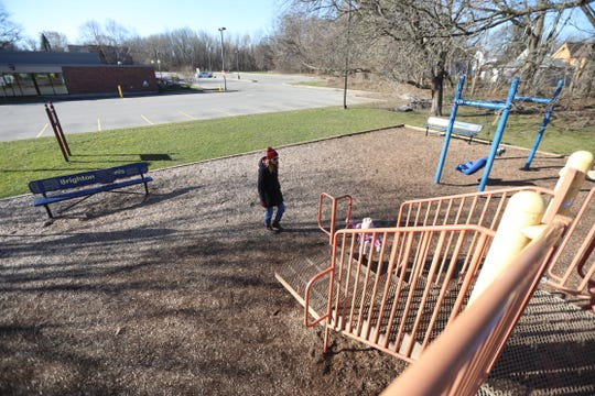 Justine Roth plays with her daughter, Zoe Hamze, 3, at the playground behind Brighton Library on March 15, 2020.