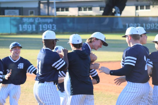 Maclay baseball players celebrate with pitcher Ryker Chavis after his recorded the final out of his perfect game against JPII on March 6.