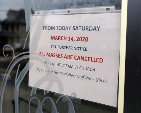 """A sign on the front door of the Church of the Holy Family in New Rochelle, reads, """"till further notice, all Masses are cancelled"""" by Order of the Archdiocese of New York, March 15, 2020."""