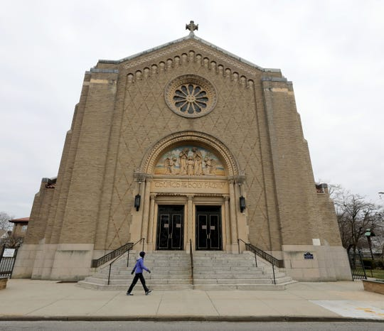 """Noelle Elia, a 64-year resident of New Rochelle, passes in front of the the Church of the Holy Family, March 15, 2020. A sign on the front door of the church reads, """"till further notice, all Masses are cancelled"""" by Order of the Archdiocese of New York."""