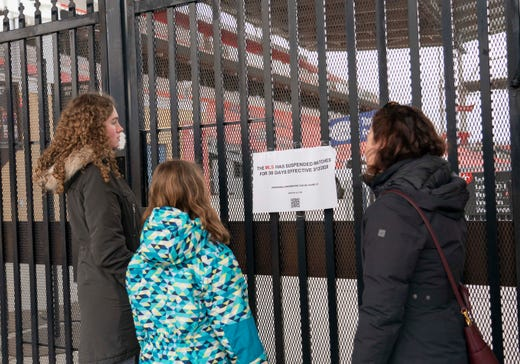 Fans read a sign posted by Major League Soccer stating the decision to suspend matches for 30 days as a precaution to minimize the spread of coronavirus COVID-19 at BMO Field, home of Toronto FC.