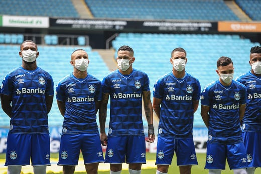 Players of Gremio wearing masks before the match between Gremio and Sao Luiz as part of the Rio Grande do Sul State Championship 2020, to be played behind closed doors at Arena do Gremio Stadium, on March 15, 2020 in Porto Alegre, Brazil. The Government of the State of Rio Grande do Sul issued a list of new guidelines to help prevent the spread of the Coronavirus which included games played with closed doors and no public. According to the Ministry of Health, as of Saturday, March 14, Brazil had 121 confirmed cases of coronavirus.