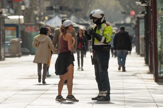 A Catalan Autonomous police officer, Mosso d'Esquadra, halts a woman who was jogging through Las Ramblas on March 15, 2020 in Barcelona, Spain. As part of the measures against the virus expansion the Government has declared a 15-day state of emergency which will come into effect today.