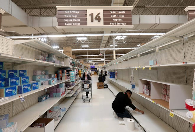 With stocks running low at grocery stores throughout the nation to due to coronavirus concerns, an employee cleans bare shelves at the Stop & Shop supermarket in Tarrytown, N.Y. March 15, 2020.