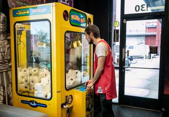 Jose Medellin tries his luck winning a roll of toilet paper from a claw machine arcade game at Wizard Hat Smoke Shop in Pflugerville, Texas, on March 15, 2020. Things look grim now with the COVID-19 outbreak and the lack of toilet paper, but America will pull through.