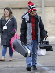 Antavious Helse, 10, is weighed down with personal items as he leaves Columbus Elementary School to get a ride home Monday with his mother Amanda Kleist. The Appleton Area School district will be closed until further notice due to statewide school closures to prevent the spread of the new coronavirus.