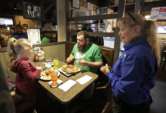 Some diners ordered corned beef early. Here, server Lisa Radichel checks in on customers Paisley and Jesse Jahnel at Spats on Monday in Appleton.