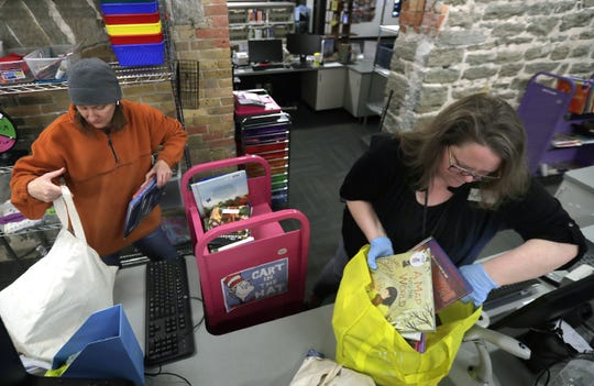 Kaukauna Public Library assistant Jody Becker, right, helps Lisa Henslin check out a stack of books Monday in anticipation of the library closing due to concerns over COVID-19. Henslin homeschools her children and uses library books as part of her curriculum.