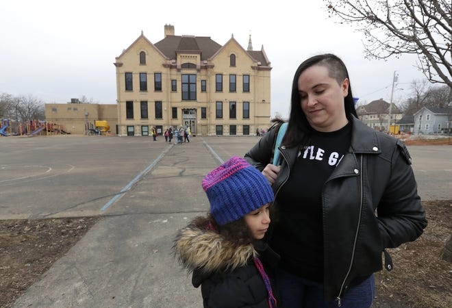 Katharina Coumbe picks up her daughter Samerika Tarrence,7, Monday at Columbus Elementary School in Appleton. The Appleton Area School district will be closed until further notice due to statewide school closures to prevent the spread of the new coronavirus.