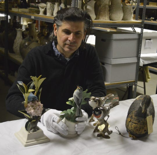 "Nicholas Ciotola, co-curator of ""Fine Feathered Friends: Birds As Mainstay And Muse"" at the New Jersey State Museum in Trenton, examines sculptures for the exhibit."