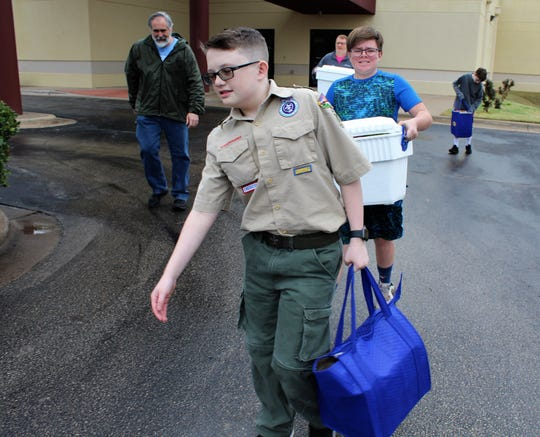 Connor Karl leads the way to a van for a Boy Scouts delivery of a Meals on Meals route Monday. Joining him were Scouts Hunter Ely and, far right, Ian McCorquodale. Scout leaders Alan Clute, left, and Troy McCorquodale said Scouts would help deliver meals while school was suspended.