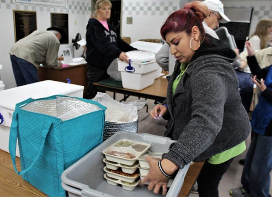 Meals on Wheels employee Jessica Andrade places packaged meals from a plastic bin in insulated soft bags for delivery Monday. Meals on Wheels is needing extra volunteers to replace seniors who are forgoing delivery because of coronavirus concerns and college students who remain on break.